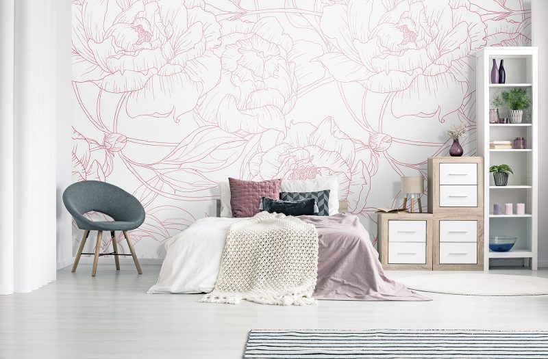 Grey armchair next to bed with pink bedsheets in pastel bedroom interior with blue posters and cabinets