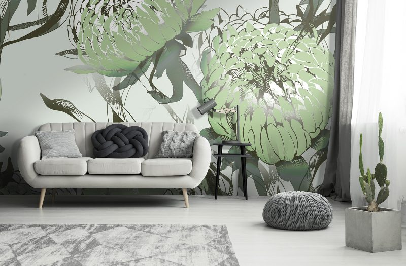 Cactus and pouf near sofa with pillows against grey textured wall with gallery in living room interior