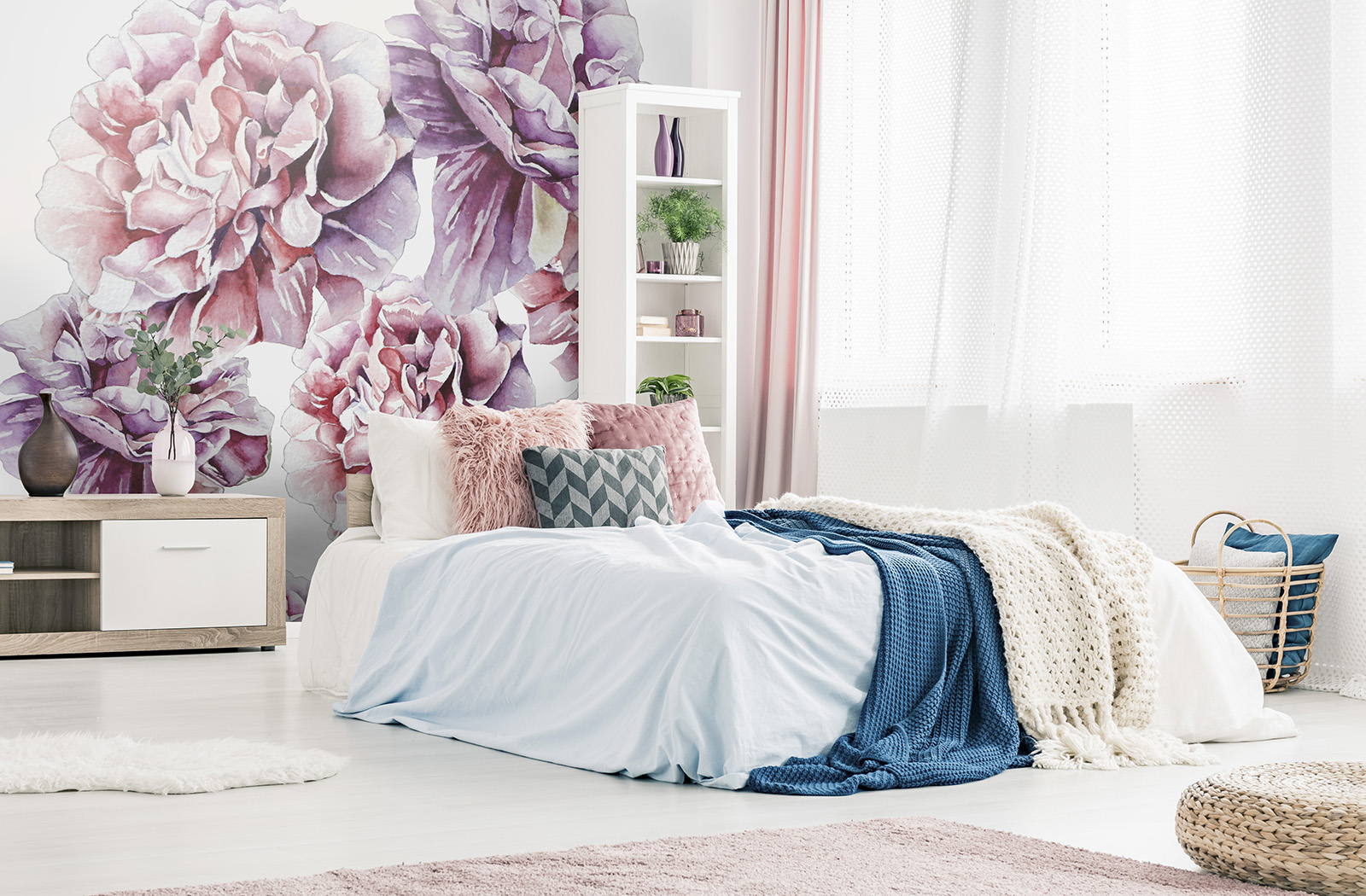 Pink pillows and blue blanket on bed in woman bedroom interior with plant on wooden cupboard