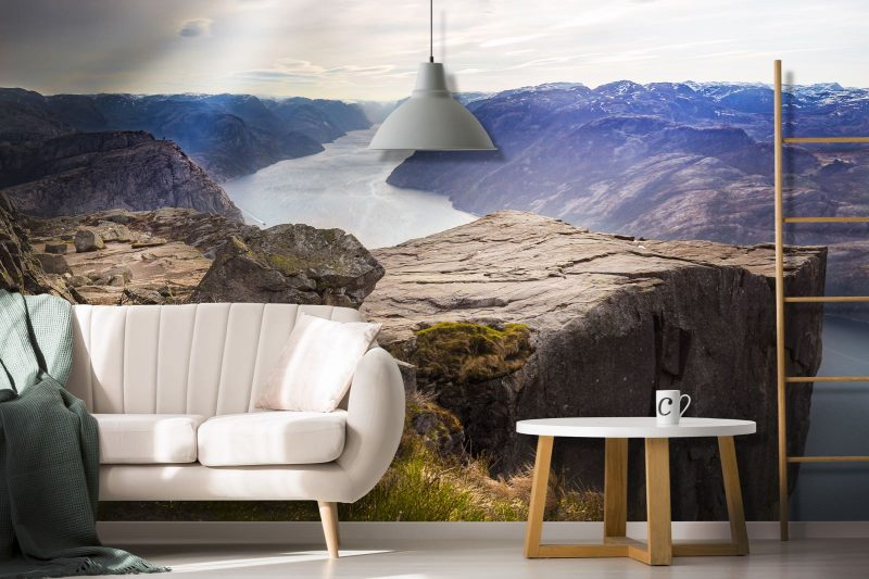 Blanket on beige sofa near wooden table against white wall with poster in apartment interior with ladder and gray lamp